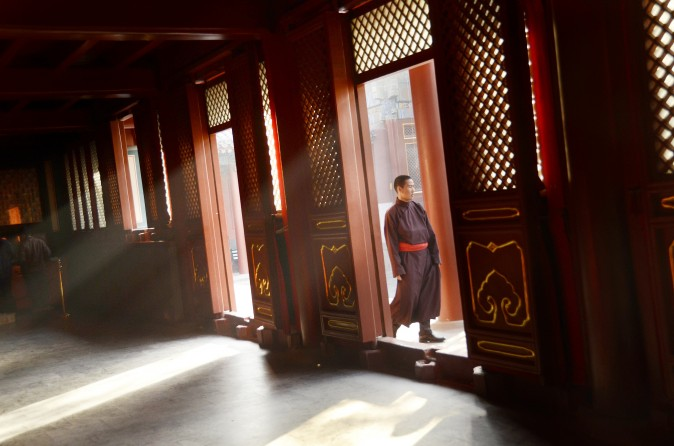 A monk walks past a doorway at the Yonghegong Lama temple in Beijing in Beijing on October 24, 2012. (Wang Zhao/AFP/Getty Images)