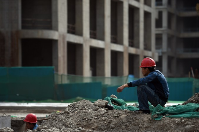 "This photo taken on May 14, 2015 shows a construction worker resting near a building in the new Yujiapu financial district, in Tianjin, in northern China. The massive government project, sometimes described as China's answer to Manhattan, incorporates dozens of skyscrapers and is being built in the hope of becoming one of the world's largest financial centers. But a slowdown in growth in China's economy has raised doubts about the viability of such large scale projects, and some reports have described the district as a ""ghost town"". (Greg Baker/AFP/Getty Images)"