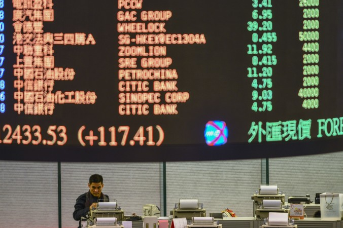 A trader walks the floor of the Hong Kong Stock Exchange as share prices are flashed above on Jan. 2, 2013. Two Hong Kong-listed companies recently lost over 40 percent of their value within a day. (Antony Dickson/AFP/Getty Images)