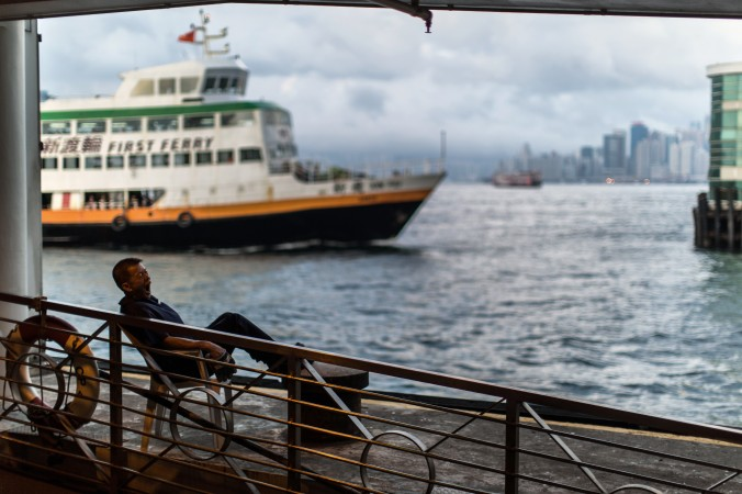 A ferry worker yawns as he waits for a commuter ferry to dock in Hong Kong on May 1. The Chinese regime's People's Liberation Army is commissioning the construction of ferries as troops transports. (Anthony Wallace/AFP/Getty Images)