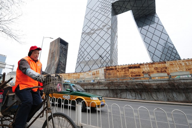 A streetsweeper rides past the CCTV Headquarters in Beijing on February 28, 2010. (FREDERIC J. BROWN/AFP/Getty Images)