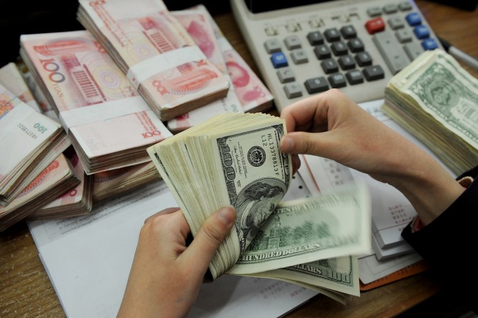 A bank teller counts stacks of US dollars and Chinese 100-yuan notes at a bank in Hefei, Anhui province, China, on Jan. 16, 2011. (STR/AFP/Getty Images)