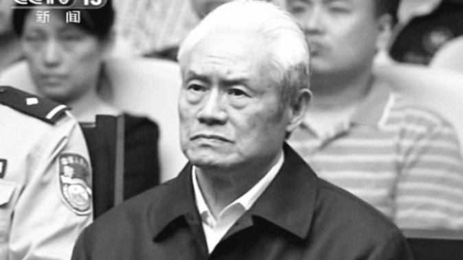 In this image taken from video released by China's CCTV, Zhou Yongkang, formerly the Chinese Communist Party Politburo Standing Committee member in charge of security, sits in a courtroom at the the First Intermediate People's Court of Tianjin in Tianjin, China, Thursday, June 11, 2015. (AP Photo/CCTV via AP Video)
