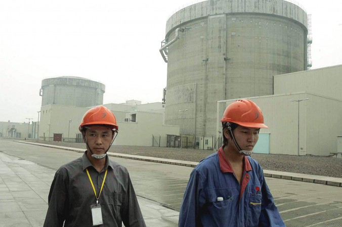 Workers walk past a nuclear power plant in Qinshan, 90 miles southwest of Shanghai, China, on June 10, 2005. (AP Photo/Eugene Hoshiko)