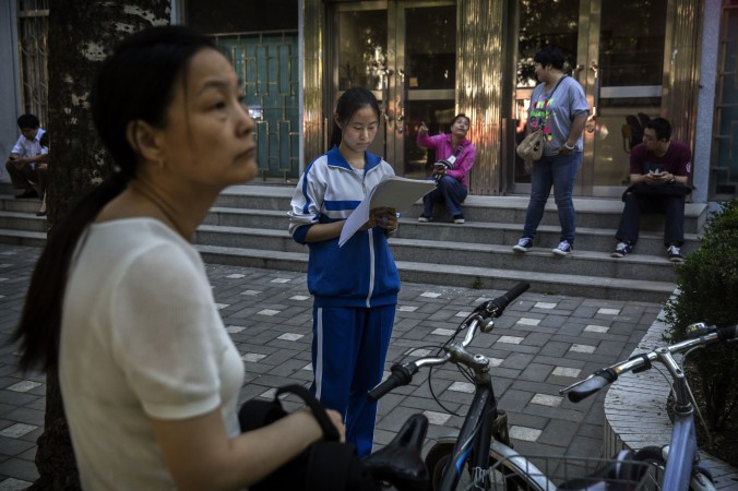 A Chinese student does some last minute studying as her mother looks on outside of the Beijing No. 4 High School, one of the most prestigious in the country, before writing the Gaokao on June 8, 2015 in Beijing, China. (Kevin Frayer/Getty Images)