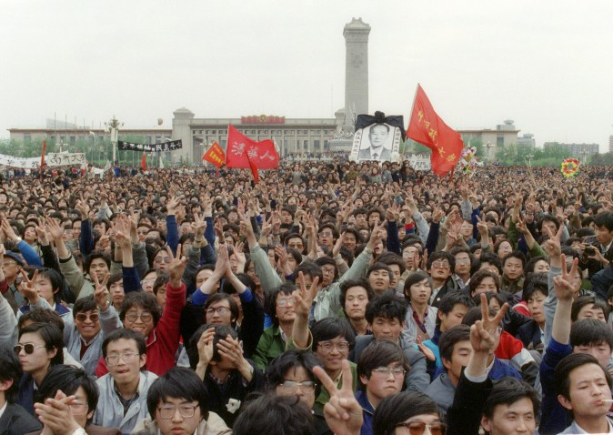 BEIJING, CHINA - APRIL 22:  Students gesture and shout slogans as they pay respect 22 April 1989 in Beijing to former Chinese Communist Party leader and liberal reformer Hu Yaobang as thousands of students gather near the monument to the People's Heroes in Tiananmen Square during an unauthorized demonstration to mourn the death of Hu Yaobang. His death in April trigged an unprecedented wave of pro-democracy demonstrations. The April-June 1989 movement was crushed by Chinese troops in June when army tanks rolled into Tiananmen Square 04 June.  (Photo credit should read CATHERINE HENRIETTE/AFP/Getty Images)