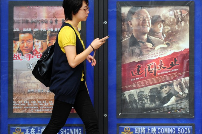 A woman walks past movie posters at a cinema in Beijing on September 16, 2009. (FREDERIC J. BROWN/AFP/Getty Images)