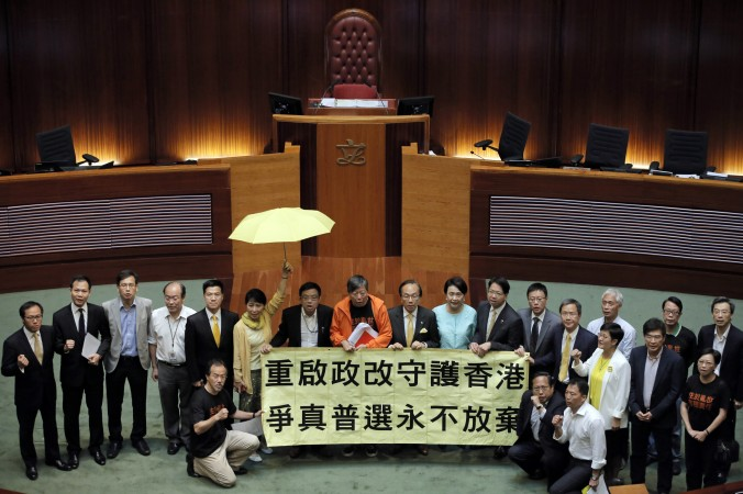 "Pro-democracy lawmakers display a yellow umbrella and a banner stating ""Reopen political reform to protect Hong Kong, never give up to fight for true universal suffrage"" after 28 lawmakers voted against the election reforms proposals at the Legislative Council in Hong Kong, June 18, 2015. (AP Photo/Vincent Yu)"