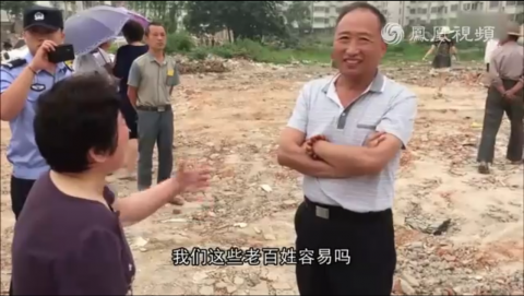 Chinese official Hua Guojun stands and laughs before Ms. Pan, while her house is demolished on June 18, 2015. (Screenshot/Phoenix Television)