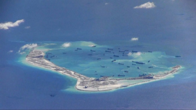Chinese dredging vessels work on the construction of an artificial island in waters around Mischief Reef in the disputed Spratly Islands in the South China Sea on May 2. The Chinese regime is allegedly deploying weapons on the man-made islands. (U.S. Navy)