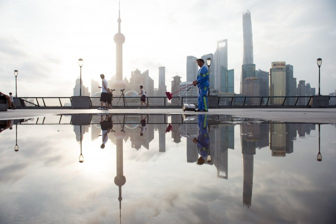 A worker cleans the promenade in Shanghai on July 24, 2014. The Chinese economy faces six major bottlenecks, according to economist He Qinglian. (Johannes Eisele/AFP/Getty Images)