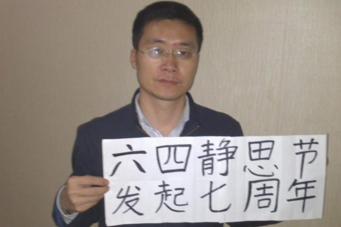 Former Chinese human rights lawyer, Tang Jingling, holds a poster in early 2014 in support of protesters killed at Tiananmen during the 1989 massacre (AP).