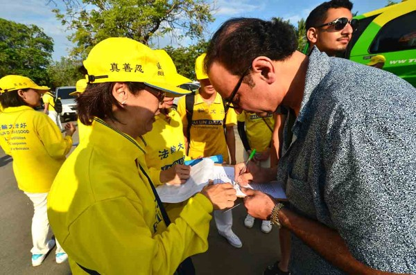A tourist signing the petition calling for an end to the persecution of Falun Gong in China (Image: Vision Times)